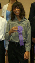Photo of Justin holding up his festival ribbon at the 2008 Music Teachers Association of California State Convention honors piano recital