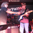 Photo of Mark Fitchett instructing a teen guitar student at the Student Rock Concert at diPiazza's in Long Beach, California