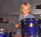 7 year old Phoenix on stage playing drums with the band on Witchy Woman at the Long Beach School of Music South Bay School of Music Student Rock Concert at diPiazzas in Long Beach California CA