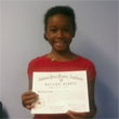 Photo of ten-year-old piano student Caroline displaying her 3rd Year National Piano Guild certificate